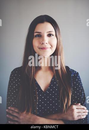 Portrait einer attraktiven jungen Geschäftsfrau, Lächeln, während allein in einem Büro mit verschränkten Armen - Stockfoto