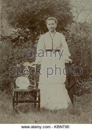 Amerikanische Archiv Schwarzweiß-Foto einer jungen Frau oder ein Mädchen neben einem Stuhl in einem Garten ein Ventilator - Stockfoto