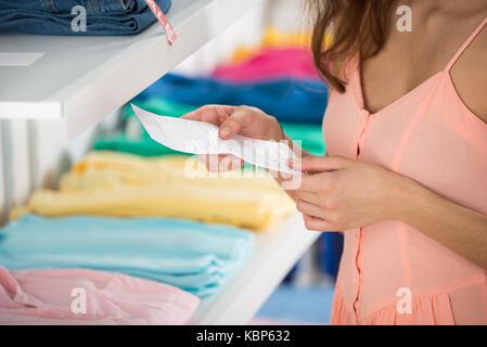 Mittelteil der jungen Frau mit Eingang im Bekleidungsgeschäft - Stockfoto