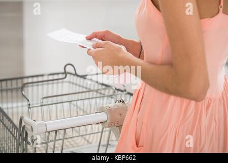 Mittelteil der jungen Frau mit Eingang im Supermarkt - Stockfoto
