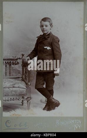 Ungeschnittene Version des Amerikanischen viktorianischen Archiv monochrome Studio portrait Foto eines Jungen tragen - Stockfoto