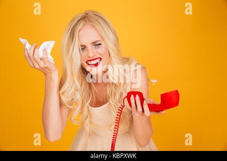 Foto von traurig Weinen schreien junge blonde Frau stehend über gelbe Wand Hintergrund sprechen per Telefon isoliert. - Stockfoto
