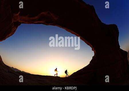 Paar Wandern am Rock-arch Al kharza, Wadi Rum, Jordanien - Stockfoto