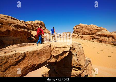 Paar Wandern am Rock - Bogen um alfrooth, Wadi Rum, Jordanien - Stockfoto