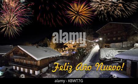 """Vorabend des neuen Jahres mit alpinen Dorf im Schnee, Feuerwerk, Text """"Feliz Ano Nuevo!' - Stockfoto"""