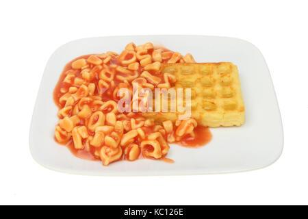 Das Kind essen, Alphabet Spaghetti und eine Kartoffel Waffel auf einer Platte gegen Weiße isoliert - Stockfoto