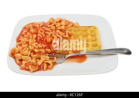 Alphabet Spaghetti und eine Kartoffel Waffeln auf einem Teller mit der Gabel gegen Weiße isoliert - Stockfoto