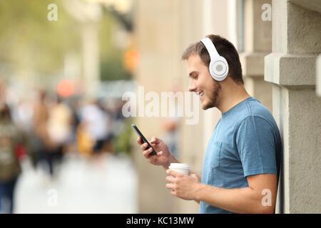 Profil von einer glücklichen Kerl hören Musik auf Linie mit Kopfhörern und einem smart phone lehnte sich an eine - Stockfoto