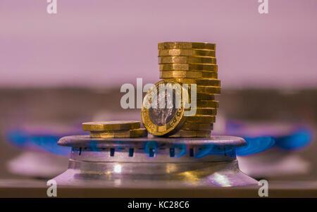Gasbrenner und neue Pfund Sterling Münzen in einem blauen Flamme. Konzept der UK die Kosten für Kraftstoff, steigende - Stockfoto
