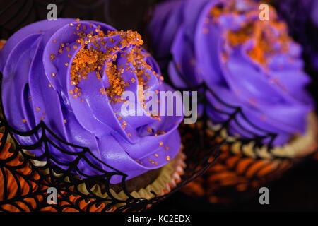 Nahaufnahme von lila Halloween Cupcakes mit orange besprüht - Stockfoto