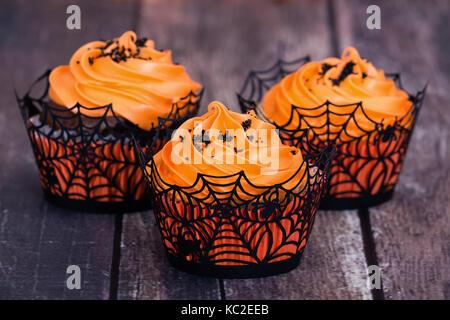Orange Halloween Cupcakes auf rustikalen Tisch - Stockfoto