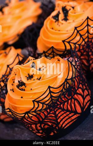 Nahaufnahme von Orange Halloween Cupcakes mit schwarzen besprüht - Stockfoto