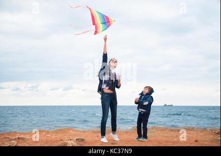 Glückliche Mutter und Kind tragen Herbst Kleidung spielen Kite auf Sturm Meer Hintergrund im Herbst - Stockfoto