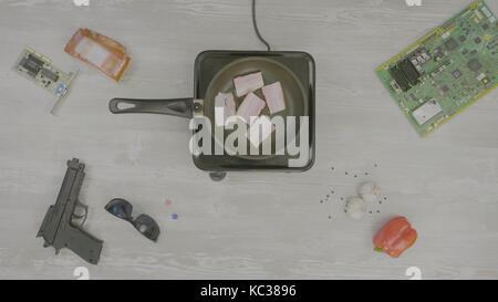 Man kocht das Fleisch in der Pfanne. Mann bereitet den Schinken in der Pfanne auf dem Tisch sind: Pistole, Gläser, - Stockfoto