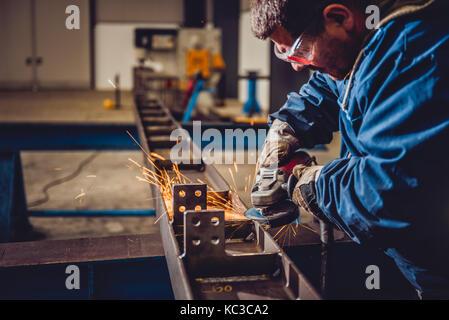 Arbeitnehmer mit Winkelschleifer in der Fabrik- und werfen Funken Stockfoto