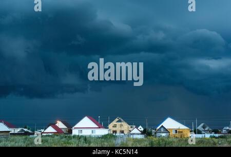 Dunkelblau und Schwarz Regenwolken über Dorf Wohnungen und Häuser wie ein Sturm beginnt - Stockfoto