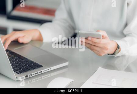 Nahaufnahme Geschäftsfrau holding Handy und Laptop auf Büro Schreibtisch, Business Communication Konzept. - Stockfoto