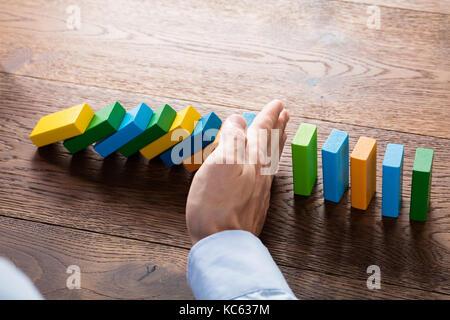 Person Hand anhalten fallende Dominosteine aus kontinuierlichen Gestürzt auf hölzernen Schreibtisch. Business Risk - Stockfoto
