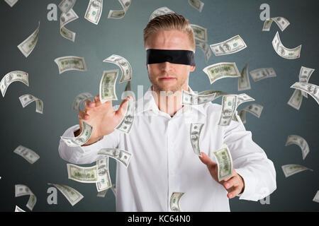 Junge Augen Geschäftsmann mit fallender Geld gegen grauer Hintergrund - Stockfoto