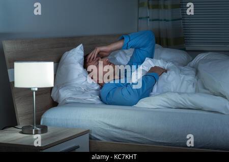 Junge Menschen leiden unter Kopfschmerzen liegen auf dem Bett in seinem Schlafzimmer - Stockfoto