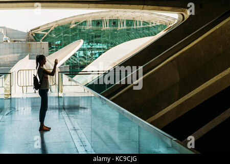 Silhouette gegen Licht der jungen Frau Fotografieren in modernes Gebäude - Stockfoto