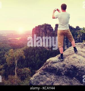 Kurze Haare Mann auf der Klippe von Rock nimmt Foto von Smart Phone von Felsen und Landschaft unten. sonnigen Abend - Stockfoto