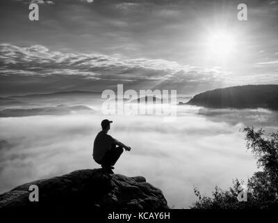 Moment der Einsamkeit. Mann auf den Felsen sitzen und beobachten in bunte Dunst und Nebel im Tal. Mann Wandern. - Stockfoto