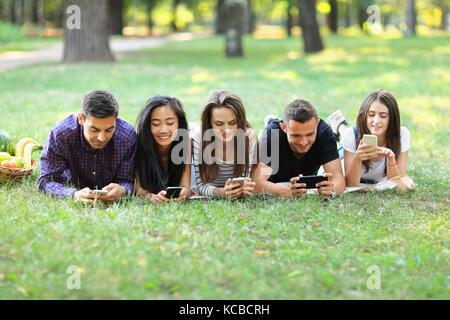Fünf junge Freunde liegen auf Gras und über Mobiltelefone. Zwei Männer und drei Frauen ruht im Freien und das Surfen - Stockfoto