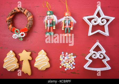 Frohe Feiertage Weihnachten Hintergrund flach mit Ornamenten auf einem roten rustikalem Holz Hintergrund. - Stockfoto