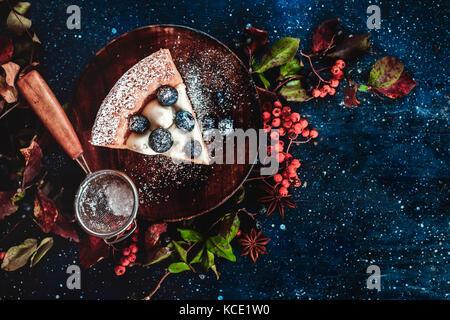 Close-up ein Stück Pumpkin Pie mit Puderzucker und ein Sieb auf einer hölzernen Platten. handgefertigte Gerichte im Herbst flach. Konzeptionelle stilisierte Essen noch leben, Table Top Shot auf dunklem Hintergrund. Stockfoto