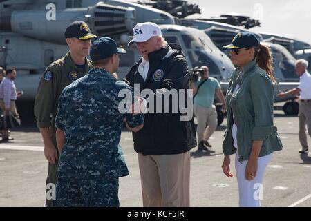 Us-Präsident Donald Trump, begleitet von der ersten Dame melania Trump, Links, begrüßt wird durch Capt. David guluzian, - Stockfoto