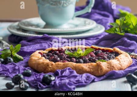 Hausgemachten blueberry Galette auf lila Tuch auf Blau Holz- Hintergrund - Stockfoto