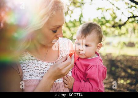 Mutter mit Baby Kommissionierung und Kirsche Essen im Garten - Stockfoto