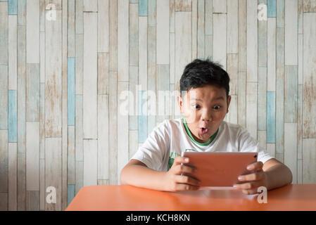 Junge asiatische Junge mit digitalen Tablet am Esstisch zu Hause mit aufgeregt Gesicht. Technologie/it-Konzept. - Stockfoto