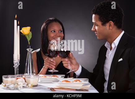 Portrait von romantisches Paar toasten rot Wein zum Abendessen - Stockfoto