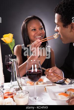 Portrait von weiblichen Fütterung Sushi zu den männlichen zum Abendessen - Stockfoto