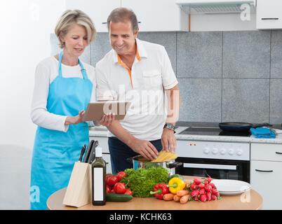 Reifer Mann und Frau auf der Suche nach Rezept tablet beim Kochen in der Küche - Stockfoto