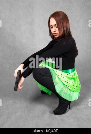 Portrait einer jungen attraktiven Frau in einem hellen Grün Rock mit einer Pistole über grauer Hintergrund - Stockfoto