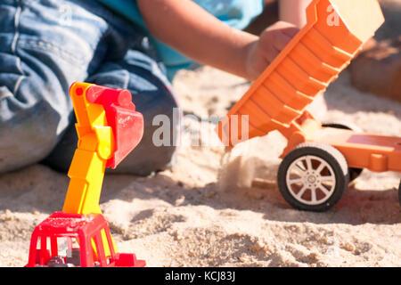 Ein Kind spielt im Sand mit großen Spielzeug Autos, Bagger, LKW - Stockfoto