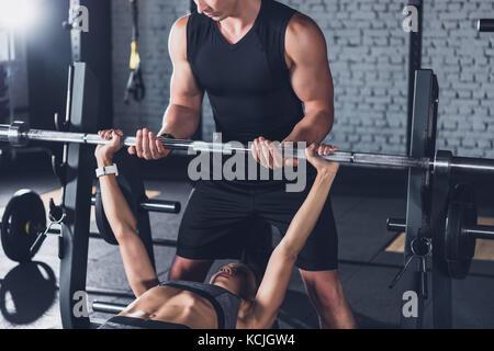 Trainer helfen Frau weightlifting - Stockfoto