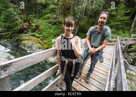Ein junges Paar wandern aus bedwell Lake kreuzt eine Fußgängerbrücke am Ende der Spur, Strathcona Park, Central - Stockfoto