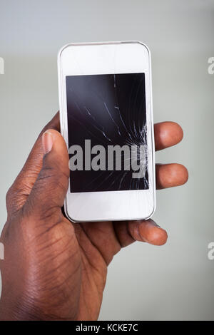 Nahaufnahme der Hand Kaufmann holding Handy mit gebrochenen Bildschirm - Stockfoto