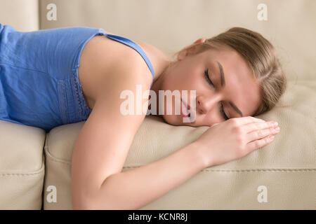 Schöne junge Frau schlafen auf der Couch, ziemlich müde Mädchen liegt schlafend auf dem Sofa, betonte Frau nap zu - Stockfoto