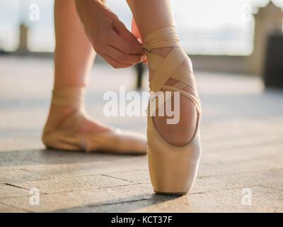 Nahaufnahme der Füße ist ein Tänzer, wie sie Praktiken Übungen auf dem Stein Damm pointe. Woman's Füße in Pointe - Stockfoto