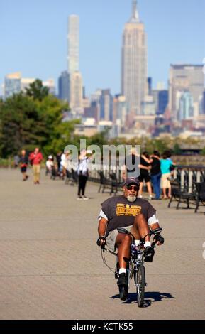 Ein Mann reiten Liegerad in Liberty State Park mit Midtown Manhattan NYC Skyline und das Empire State Building im - Stockfoto