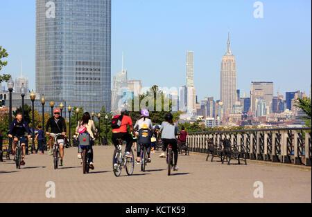 Besucher Radfahren in Liberty State Park mit Goldman Sachs Turm und Midtown Manhattan Skyline und das Empire State - Stockfoto