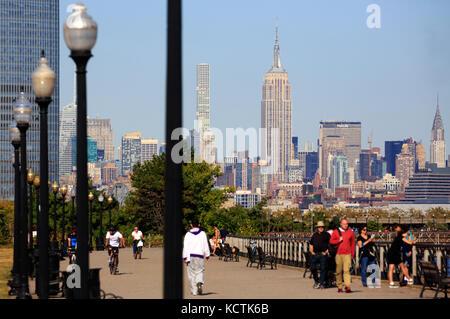 Besucher am Hudson River Uferpromenade in Liberty State Park mit Midtown Manhattan NYC Skyline und das Empire State - Stockfoto