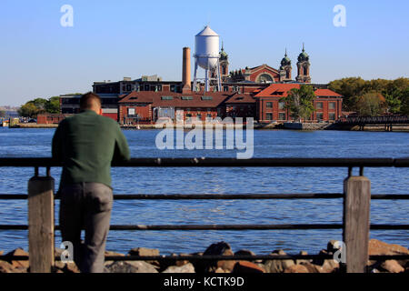 Ein Mann, der an der Liberty State Park mit historischen Ellis Island immigrant Prüfplatz im Hintergrund. New Jersey - Stockfoto
