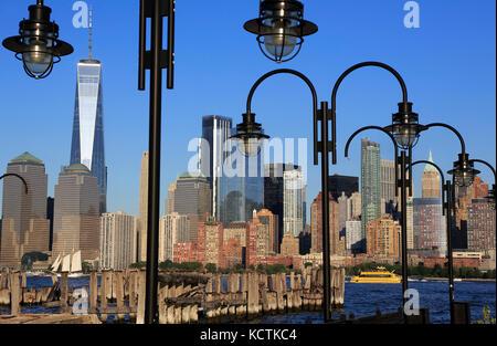 Skyline von Financial District in Manhattan mit Hudson River und Strassenlaternen von alten Fähranleger von Liberty - Stockfoto