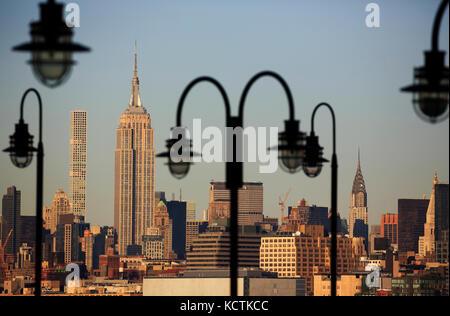 Empire State Building und Skyline von Midtown Manhattan, eingerahmt durch die Laternenpfosten der alten Fähranlegestelle - Stockfoto